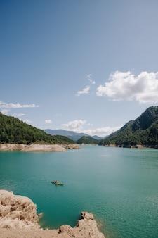 Cena de caiaque em um dia ensolarado em um lago de água azul, rodeado por montanhas no verão