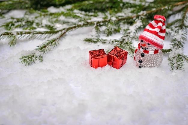 Cena de conto de fadas de inverno de natal com um boneco de neve de brinquedo com boné e lenço com os melhores presentes em caixas vermelhas na neve com espaço de cópia