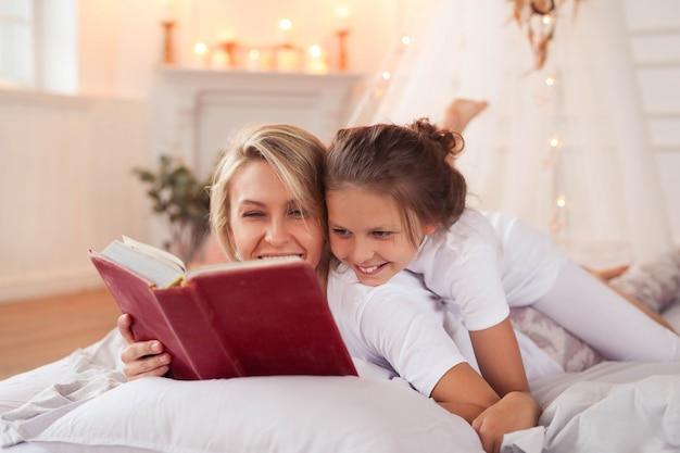 Cena de família. feliz mãe e filha em uma cama