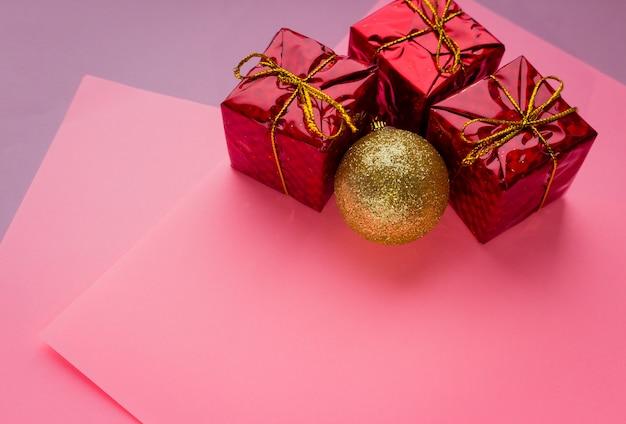 Cena de feriado de natal - ouro brilhante bugiganga, caixas de presente vermelha em fundo rosa com copyspace