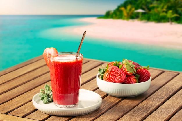 Cena de férias com smoothie de morango e praia tropical