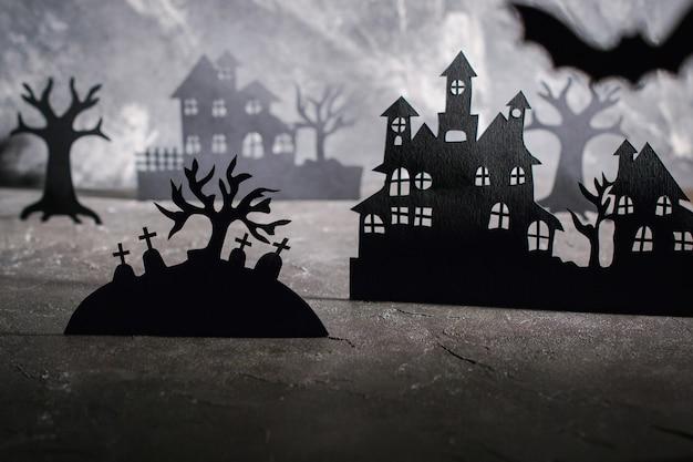 Cena de halloween. casas de papel e árvores escuras e enevoadas no cemitério