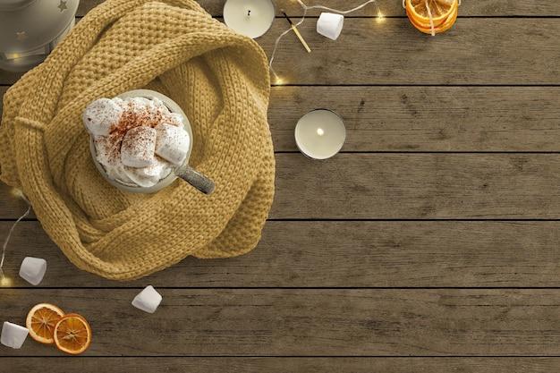 Cena de inverno aconchegante com luzes de fadas, marshmallows, velas e cobertor