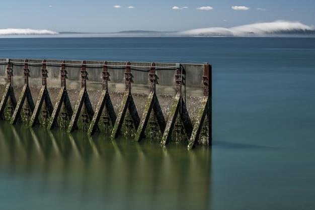 Cena de longa exposição da paisagem aquática de um velho paredão cercado por água do mar macia