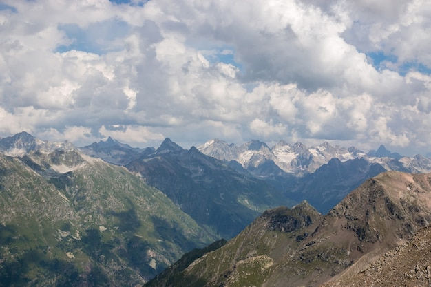 Cena de montanhas com céu nublado dramático no parque nacional de dombay, cáucaso, rússia. paisagem de verão e dia ensolarado