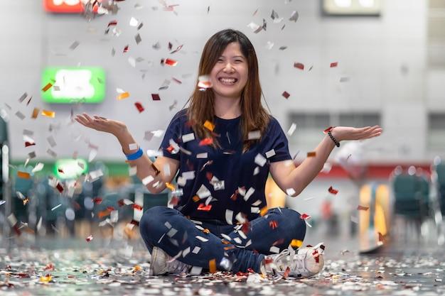 Cena de mulher asiática atraente comemorando e jogando com confete na sala