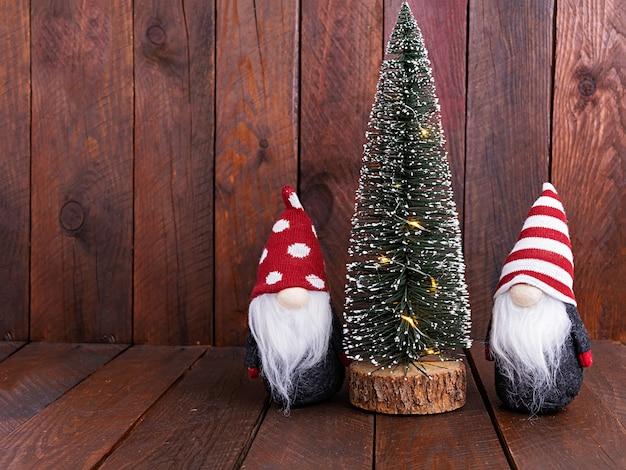 Cena de natal. árvore do abeto com luzes de natal e anões.
