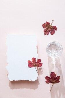 Cena de natureza morta com uma folha de papel em branco e folhas coloridas de outono e um copo de água de cristal