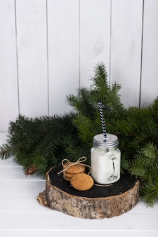 Cena de natureza morta de natal. vela perfumada em uma jarra de vidro e biscoitos em uma grossa tora de madeira perto de um galho de abeto
