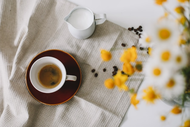 Cena de natureza morta de verão com flores silvestres, xícara de café e jarra de leite na mesa branca