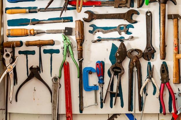 Cena de oficina. prateleira velha das ferramentas contra uma tabela e uma parede. estilo de garagem