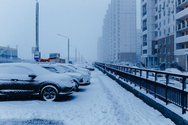Cena de rua da cidade de neve do inverno. carros cobertos de neve na rua de inverno na rússia.