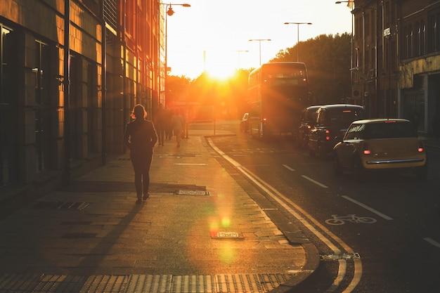Cena de rua de pessoas andando durante o pôr do sol na rua oxford
