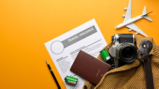 Cena de simulação criativa, vista superior da bolsa de viagem com câmera, passaporte, formulário de seguro de viagem e itens de viagem