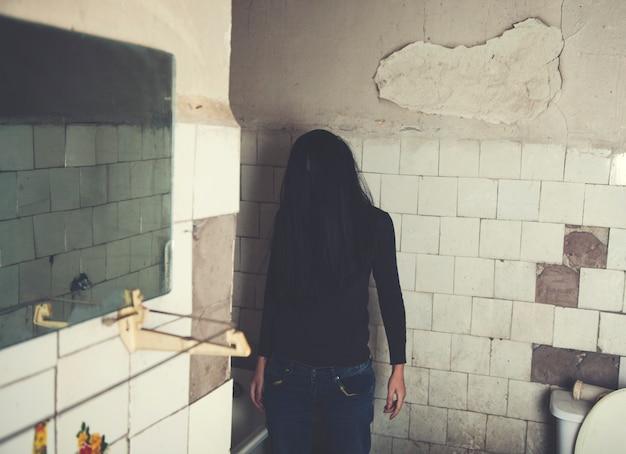 Cena de terror da mulher assombrada em pé no prédio demolido