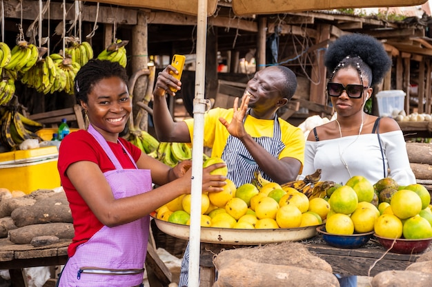 Cena do mercado local com comerciantes satisfeitos vendendo, um deles usando seu telefone para fazer videochamada