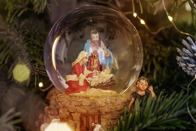 Cena do nascimento de jesus cristo em uma bola de vidro em uma árvore de natal