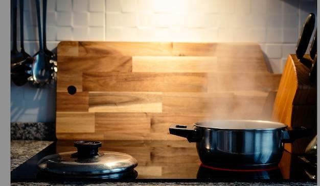 Cena doméstica de um forno do vapor que cozinha o potenciômetro em uma cozinha elétrica com uma tabela de madeira no fundo.