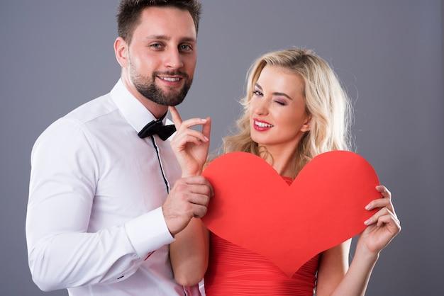 Cena engraçada de homem e mulher com coração de papel