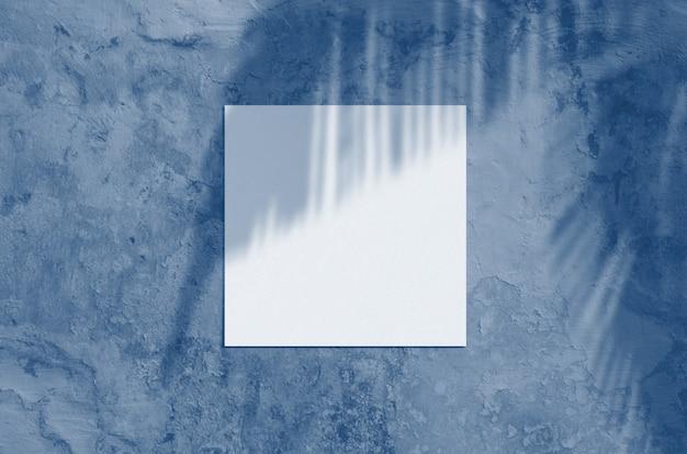 Cena moderna da superfície dos artigos de papelaria da luz solar do verão. vista plana leiga em branco cartão com sombra de folha de palmeira e ramos sobreposição em fundo grunge. cor azul clássica. cor do ano 2020.