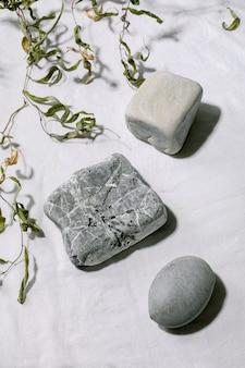 Cena natural abstrata com diferentes pedras geométricas como pódio ou pedestais para apresentação de produtos ou exposições em tecido branco com decoração de galho. cena para mostrar qualquer produto para publicidade.