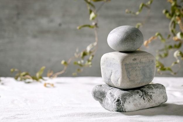 Cena natural abstrata com pedras geométricas como pódio de equilíbrio ou pedestais para apresentação de produtos ou exposições em tecido branco com decoração de ramo. cena para mostrar qualquer produto para publicidade.