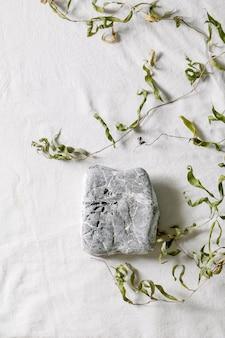 Cena natural abstrata com pedras geométricas como pódio ou pedestais para apresentação de produtos ou exposições em tecido branco com decoração de ramo. cena para mostrar qualquer produto para publicidade. postura plana