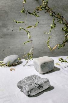 Cena natural abstrata com pedras geométricas como pódio ou pedestais para apresentação de produtos ou exposições em tecido branco com decoração de ramo. cena para mostrar qualquer produto para publicidade.