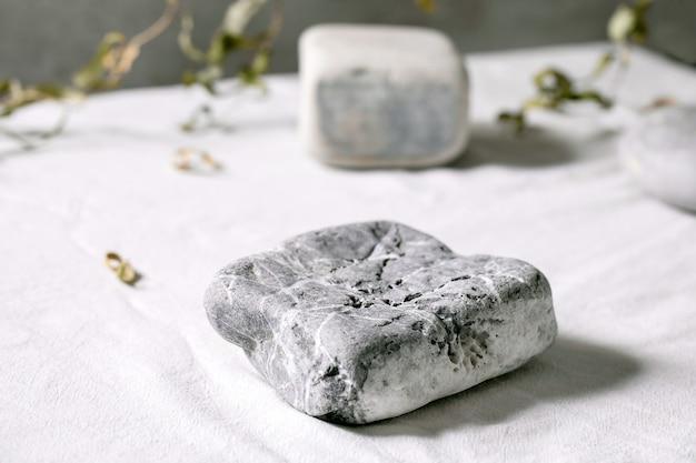 Cena natural abstrata com pedras geométricas como pódio ou pedestais para apresentação de produtos ou exposições em tecido branco com decoração vegetal. cena para mostrar qualquer produto para publicidade.