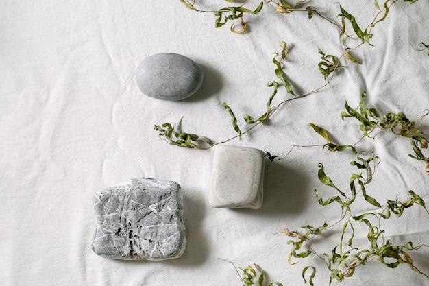 Cena natural abstrata com três pedras geométricas como pódio ou pedestais para apresentação de produtos ou exposições em tecido branco. cena para mostrar qualquer produto para publicidade. postura plana