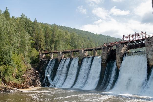 Cena natural com água caindo da enorme ponte de pedra em um grande rio no fundo de árvores verdes e céu nublado