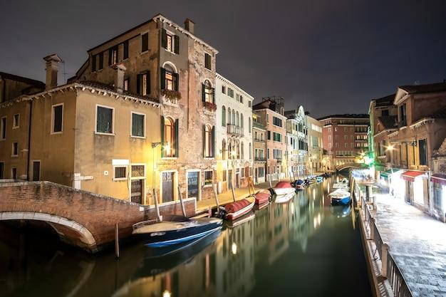 Cena noturna de edifícios antigos iluminados, barcos flutuantes e reflexos na água do canal em veneza, itália.