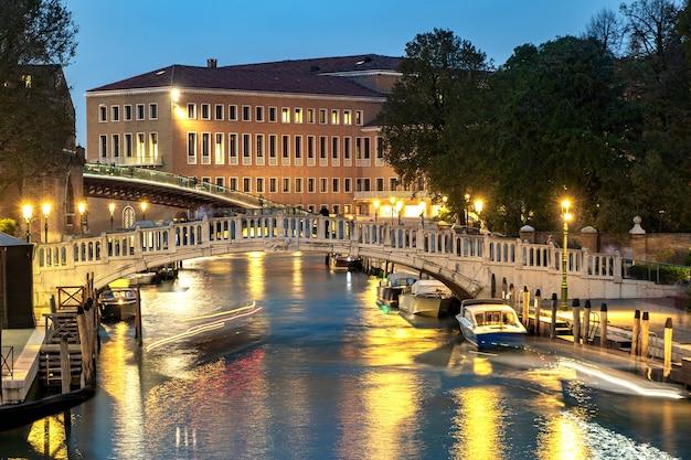 Cena noturna de edifícios antigos iluminados, barcos flutuantes e reflexos na água do canal em veneza