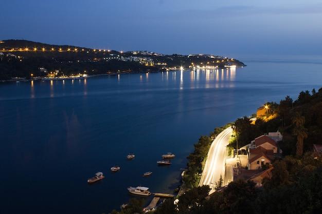 Cena noturna na baía de spit, na croácia. tiro de longa exposição com muitas luzes e trilhas de tráfego. famosa estância turística europeia no mar adriático.
