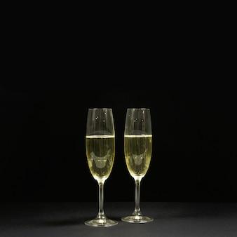Cena preta com duas taças de champanhe.