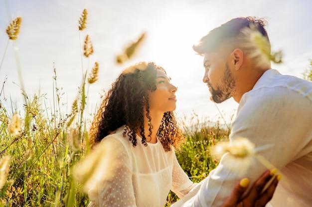 Cena romântica de jovem casal apaixonado, multirracial e apaixonado, olhando-se nos olhos entre a vegetação alta ao pôr do sol ou ao amanhecer com efeito de luz de fundo do sol foto de sonho romântico de amantes na natureza