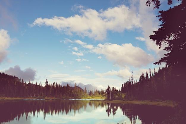 Cena serena à beira do lago da montanha com reflexo das rochas nas águas calmas.