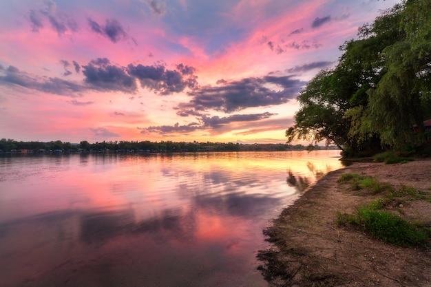 Cena tranquila com rio e céu colorido com nuvens ao pôr do sol