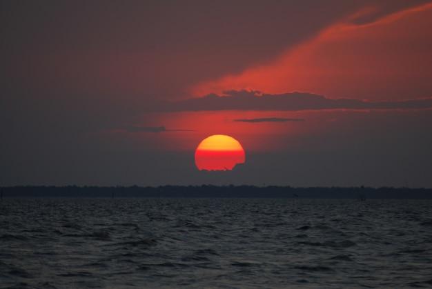 Cena tranquilo do sol vermelho do close up e do por do sol vermelho do céu sobre o oceano em bangpu tailândia.