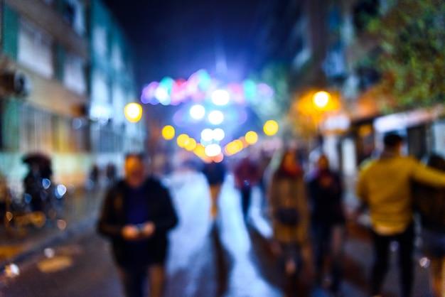 Cena urbana da noite com os povos que andam fora de foco com fundo colorido.