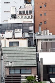 Cena urbana vertical cheia de unidades de ar-condicionado na parte de trás dos edifícios modernos de tóquio