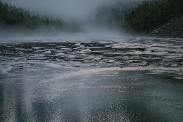 Cenário alpino atmosférico com lago de montanha e córregos de água no fundo da silhueta da floresta em nuvens baixas. paisagem cênica das montanhas com riachos de montanha e silhuetas de árvores no nevoeiro ao entardecer.