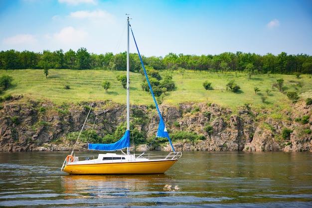 Cenário bonito do iate da navigação com costa rochosa sobre.