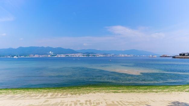 Cenário da costa marítima na ilha de miyajima, onde o santuário de itsukushima está localizado, com vista para o terminal de balsas, as atividades na baía e a cidade de hiroshima ao fundo, japão