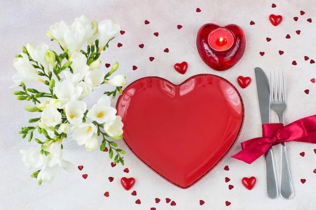 Cenário da mesa: prato vermelho em forma de coração, uma vela em um castiçal, talheres e um buquê de frésia