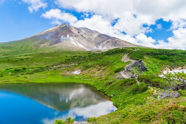 Cenário da montanha do pico de asahidake com água da reflexão e o céu nebuloso azul no verão, asahikawa, hokkaido, japão.
