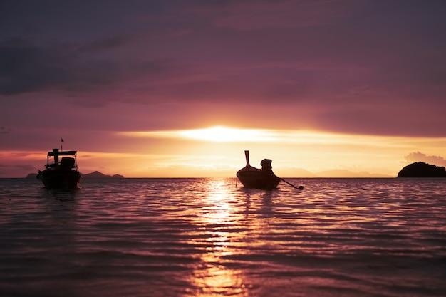 Cenário da praia da natureza nas horas de verão com o céu do crepúsculo do por do sol de muitos barcos.