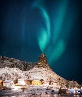 Cenário da vila de pescadores norueguesa cercada com neve coberta de montanhas
