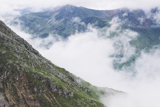 Cenário de fumaça saindo das montanhas no meio de uma vista verde