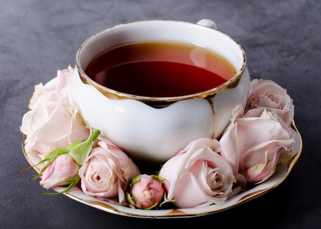 Cenário de hora do chá com xícara de chá de porcelana branca vintage, rosas cor de rosa suaves